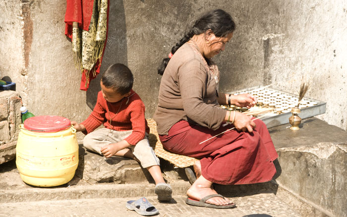 Kathmandu - Woman preparing butter lamps at Swayambhunath