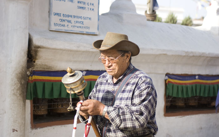 Bodhnath Stupa - Tibetan walking the cora with his prayer wheel and prayer chain